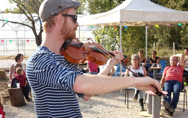 Homme qui joue du violon devant du public